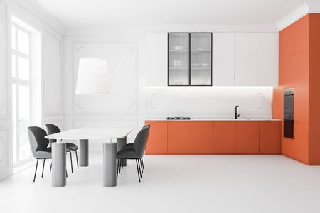 Interior of luxury kitchen with white walls and floor, white cupboards, orange countertops, two built in ovens and massive marble dining table with gray chairs. 3d rendering