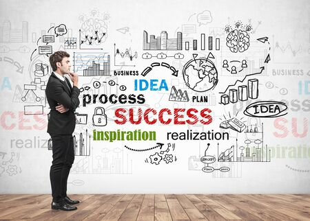 Side view of handsome young businessman standing near concrete wall with colorful business success sketch drawn on it. Concept of brainstorming and business planning Фото со стока - 131318827