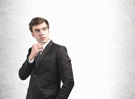 Portrait of thoughtful young businessman with short dark hair in stylish suit standing near concrete wall. Concept of management and decision making. Mock up Banco de Imagens - 131318830