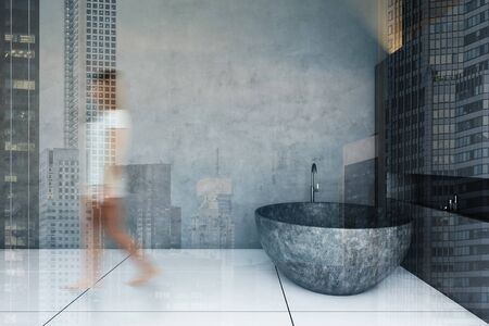 Blurry young woman walking in loft bathroom with gray and concrete walls, tiled floor and stone bathtub. Toned image double exposure Stok Fotoğraf
