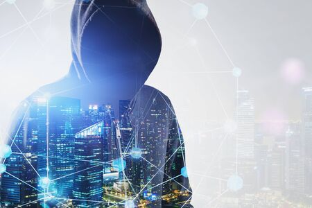 Close up of young hacker in hoodie standing in night city with double exposure of network interface. Concept of cybercrime. Toned image copy space Banco de Imagens