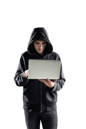 Isolated portrait of concentrated young hacker or programmer in black hoodie using laptop computer. Concept of cyber security and data protection.