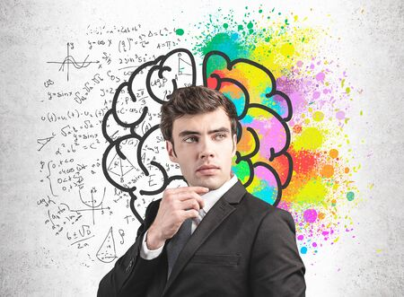 Thoughtful young man in suit standing near concrete wall with brain sketch with formulas drawn on it. Concept of logic and creativity. Science and creative approach in business