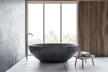 Interior of stylish bathroom with concrete and wooden walls, white tiled floor, round stone bathtub and chair with towels. 3d rendering Stok Fotoğraf