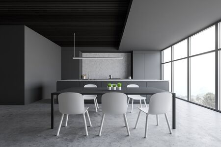Interior of modern kitchen with grey and concrete walls, concrete floor, large window with mountain view, gray dining table with chairs, island with built in sink and gray countertops. 3d rendering