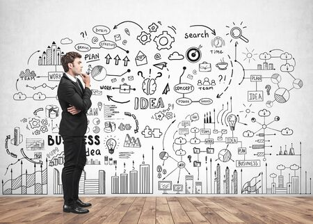 Handsome young businessman thinking near concrete wall with business strategy sketch drawn on it. Concept of business planning