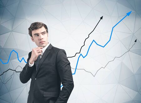 Handsome young businessman in dark suit standing near gray wall with increasing graphs. Concept of business success and trading. Фото со стока - 131319087