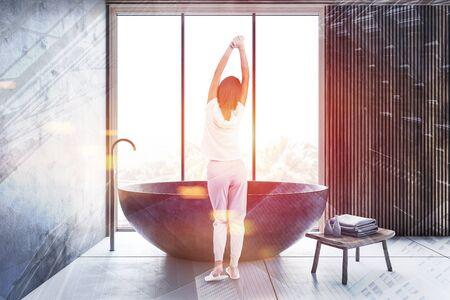 Young woman standing in luxury bathroom with gray and wooden walls, tiled floor, large window and stone round bathtub. Toned image double exposure