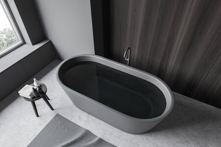 Top view of grey bathtub with water standing in modern bathroom with gray and dark wooden walls, concrete floor and gray carpet. 3d rendering Stock Photo