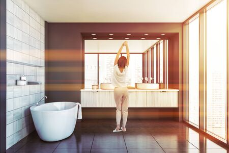 Rear view of young woman standing in modern bathroom interior with gray and wooden tile walls, comfortable bathtub and double sink. Toned image