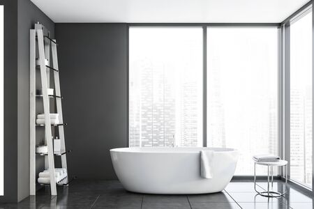 Interior of bathroom with gray walls, panoramic windows with cityscape, tiled floor, comfortable white bathtub and shelves with towels and creams. 3d rendering