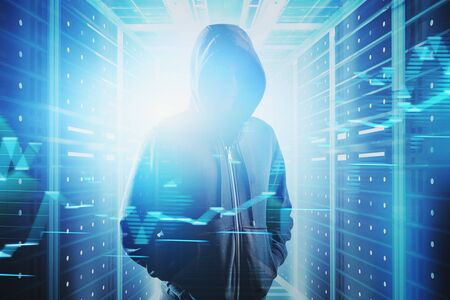 Young hacker in black hoodie standing in blurry server room with double exposure of graphs. Concept of cyber crime and data theft. Toned image Banque d'images - 131319327