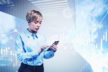 Serious young blonde trader using smartphone in city with double exposure of forex graphs. Concept of stock market. Toned image Фото со стока - 131319332