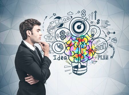 Side view of handsome young businessman standing near gray wall with colorful business idea sketch drawn on it. Concept of brainstorming, startup and creative thinking