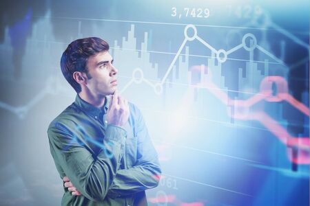 Pensive young handsome broker looking at digital graphs. Concept of market analysis and investment. Toned image double exposure Фото со стока