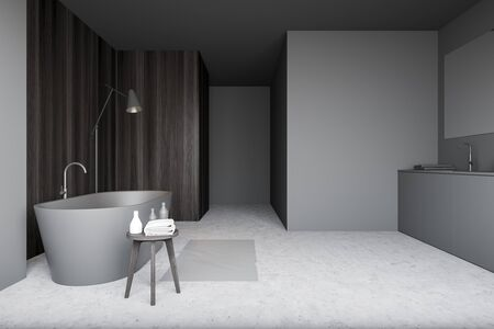 Interior of minimalistic bathroom with gray and dark wooden walls, concrete floor, chair with towels, comfortable grey bathtub, sink and floor lamp. 3d rendering