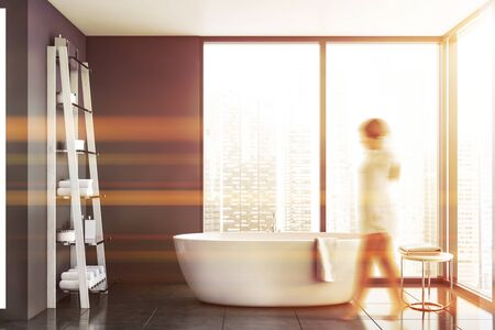 Blurry young woman walking in panoramic bathroom with gray walls, tiled floor, comfortable bathtub and shelves with towels. Concept of spa. Toned image