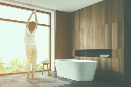 Rear view of woman in pajamas standing in stylish bathroom with wooden walls, tiled floor, panoramic window with tropical view and comfortable bathtub. Toned image double exposure