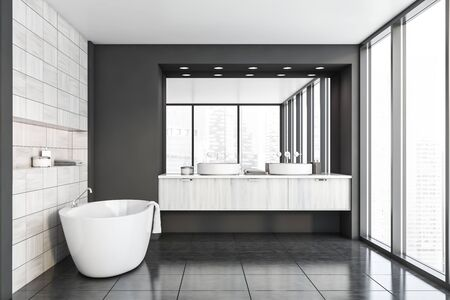 Interior of original bathroom with gray and wooden tiled walls, tiled floor, panoramic window with cityscape, comfortable bathtub and double sink with large mirror. 3d rendering