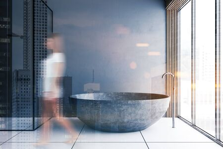 Blurry young woman walking in loft bathroom with gray walls, tiled floor, shower stall and stone bathtub. Toned image double exposure Reklamní fotografie