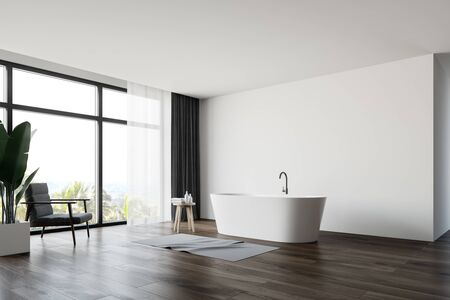 Interior of spacious bathroom with white walls, wooden floor, large window with tropical view and comfortable white bathtub with gray armchair near it. 3d rendering