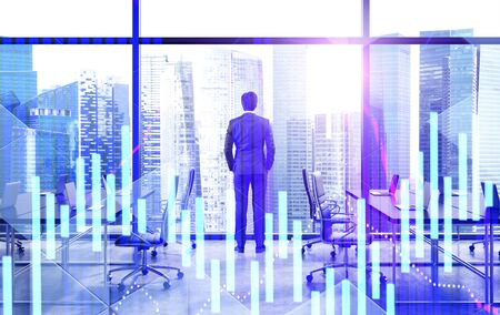 Young businessman looking at city from panoramic office window with double exposure of digital graphs. Concept of stock market and leadership. Toned image