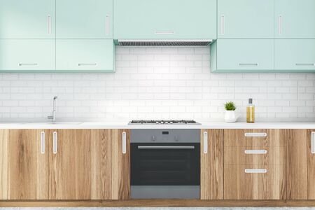 Close up of wooden kitchen countertops with built in stove and sink and blue cupboards above them in modern white brick room. 3d rendering