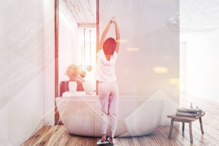 Rear view of young woman standing in modern bathroom interior with white walls, wooden floor, comfortable bathtub and bedroom in background. Toned image double exposure
