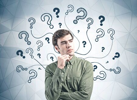 Thoughtful young man in green shirt standing near gray wall with question marks drawn on it. Concept of problem solving and curiosity Imagens
