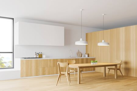 Cozy wooden dining table with chairs standing in modern kitchen corner with white and wooden walls, white cupboards and wooden countertops. 3d rendering Фото со стока