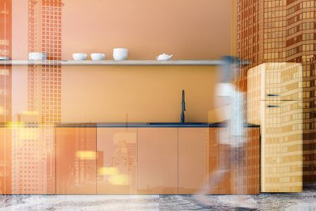 Blurry young woman walking in modern kitchen with bright orange walls, marble floor, orange countertops with sink, yellow fridge and long shelf with dishes. Toned image double exposure