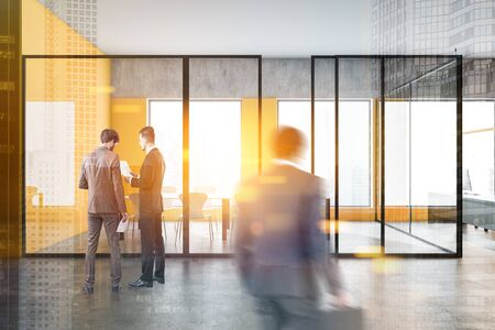 Business people walking in modern office lobby with yellow and concrete walls, conference room and open space area. Corporate lifestyle concept. Toned image double exposure blurred