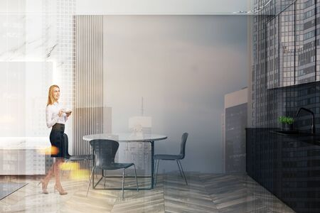 Smiling young woman with coffee standing in modern kitchen interior with beige and marble walls, wooden floor, round table and gray countertops with sink. Toned image double exposure