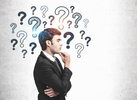Handsome young businessman standing near concrete wall with question marks drawn on it. Concept of brainstorming and looking for answers. Mock up Imagens