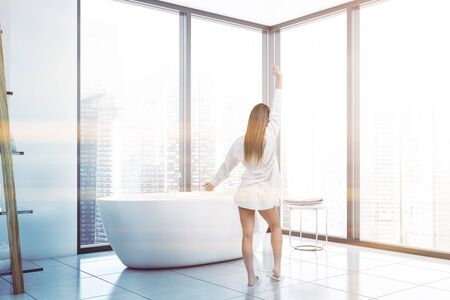 Rear view of woman in nightgown standing in panoramic bathroom with white walls, tiled floor and comfortable bathtub. Concept of spa. Toned image Stok Fotoğraf