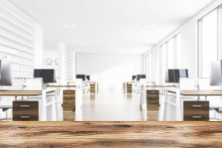 Blurry modern consulting company open space office with white walls, tiled floor and rows of dark wooden computer tables. Wooden desk for your product in foreground. 3d rendering