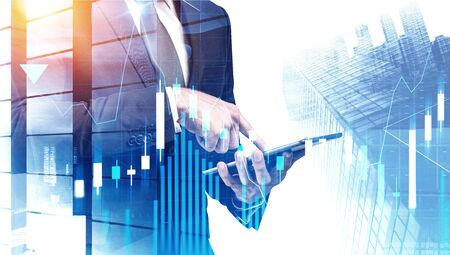 Young businessman using tablet computer in modern city with double exposure of forex graphs. Concept of stock market. Toned image