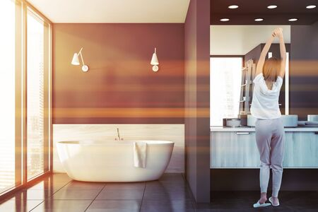 Young woman in pajamas standing in modern bathroom interior with panoramic window, dark gray walls, tiled floor, comfortable bathtub and sink. Toned image