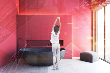 Rear view of young woman in pajamas standing in luxury bathroom with red walls and stone round bathtub. Concept of spa. Toned image double exposure