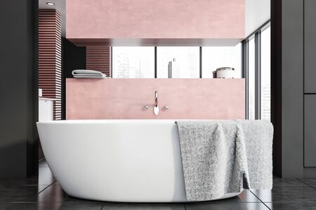 Interior of modern bathroom with gray and pink walls, tiled floor, comfortable bathtub with mirror above it and pink shelves with towels and beauty products. 3d rendering Фото со стока