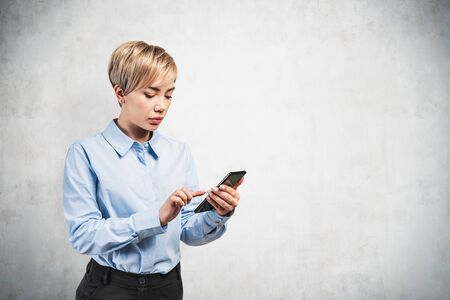 Beautiful young businesswoman with short blond hair wearing formal clothes using smartphone standing near concrete wall. Concept of communication and internet. Mock up Stock fotó