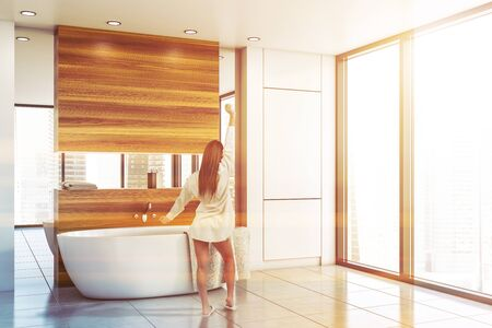 Rear view of woman in nightgown standing in panoramic bathroom interior with white and wooden walls, tiled floor, comfortable bathtub and mirror. Toned image Stok Fotoğraf
