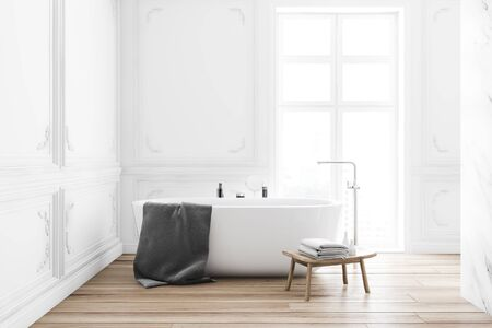Interior of classic style bathroom with white marble walls, wooden floor, comfortable bathtub with gray towel on it near big window and table with beauty products. 3d rendering