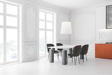 Corner of luxury kitchen with white walls and floor, white cupboards, orange countertops and massive marble dining table with gray chairs. 3d rendering Stock Photo