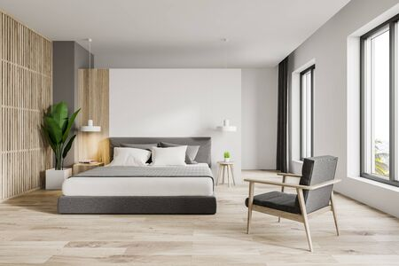 Interior of modern master bedroom with white and wooden walls, wooden floor, comfortable king size bed with bedside table and armchair. 3d rendering 版權商用圖片