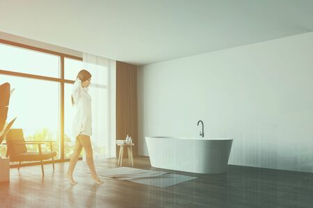 Beautiful young woman in nightgown walking in luxury panoramic bathroom with white walls, wooden floor, comfortable bathtub and armchair. Toned image double exposure