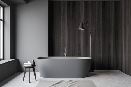 Interior of minimalistic bathroom with gray and dark wooden walls, concrete floor, chair with towels, comfortable grey bathtub and floor lamp. 3d rendering