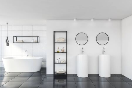 Interior of stylish bathroom with white tile walls, gray floor, comfortable bathtub, round double sink with two mirrors and shelves with beauty products. 3d rendering Фото со стока