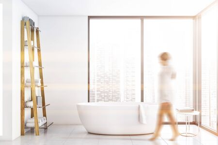 Blurry young woman walking in panoramic bathroom with white walls, tiled floor, comfortable bathtub and shelves with towels. Concept of spa. Toned image Stok Fotoğraf