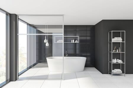 Interior of stylish bathroom with gray tile and glass walls, white floor, comfortable bathtub and shelves with towels and beauty products. 3d rendering